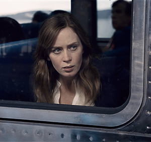 A grown woman stares out a train window